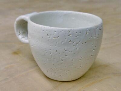 和の装飾技法が施された白いコーヒーカップ。日本の陶器ですね。